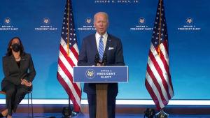 En man i blå kostym och blå slips står vid ett podium, bakom honom syns två amerikanska flaggor. Till vänster en kvinna i granitgrå kostym och svart munskydd. Hon sitter på en stol.