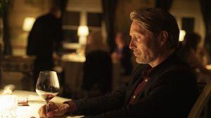 Närbild på Martin (Mads Mikkelsen) som sitter vid en bord med ett glas rödvin.