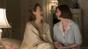 Katharine Graham (Meryl Streep) och dottern Lally Graham (Alison Brie) sitter bredvid varandra på sängen och skrattar.