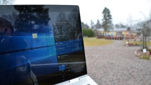 Närbild på en bärbar dator med en park i bakgrunden.