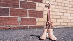 en leksaks giraff med två plast männsiko fötter på frambenen.