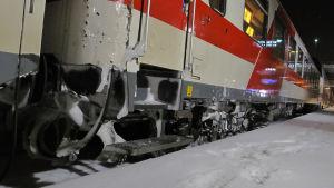 Tåg som står i snöväder.