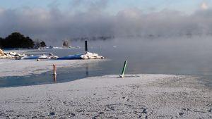 Isen lägger sig utanför Kitö bro i Sibbo skärgård, Kalvön i Borgå skärgård skymtar bakom sjöröken