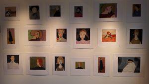 Flera konstverk hänger på en vägg. Det är barn som har ritat av kända verk av Helene Schjerfbeck.