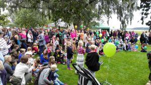Många barn och vuxna står i en park och lyssnar på en konsert.