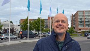 Universitetslektor Jan-Erik Mansikka poserar framför flaggor på Yles parkeringsplats.