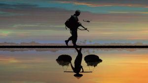 Soldat i solnedgång med helikopter i bakgrunden.