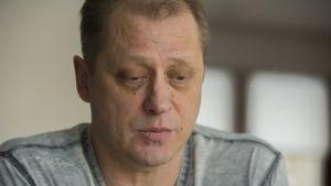 Lars Backlund sitter iklädd grå t-skjorta hemma vid köksbordet.