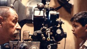 Koneenkäyttäjä Alfredo (Philippe Noiret) Totò (Salvatore Cascio) elokuvateatterin konehuoneessa elokuvassa Cinema Paradiso