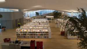 Helsingin keskustakirjasto Oodin 3. kerros. Avarassa tilassa on kumpuileva valkonen katto, puisella parkettilattialla on useita valkoisia kirjahyllyjä. Punaisia muuttolaatikoita on muutamassa pinossa.