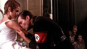 Natsiupseeri suutelee nuoren naisen kättä, taustalla kaksi keskitysleirivankia katselee. Kuva elokuvasta Yöportieri.