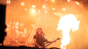 Tom Araya på scenen med Slayer. I bakgrunden är det stora eldsflammor från pyrotekniken.