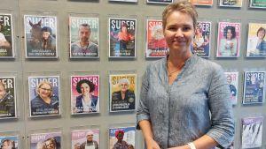 Kvinna står framför en vägg med tidningar.