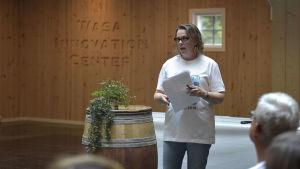 en kvinna med glasögoin pratar till en publik