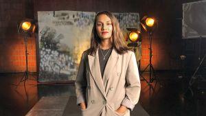 Susani Mahadura seisoo studiossa taustalavasteen ja studiolamppujen edessä. Kuva otettu lyhytvideosarjaan Me elokuvantekijät.