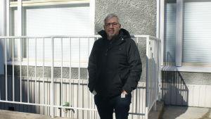 Michael Lindholm framför ett höghus.
