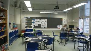 Jasmin Bilenberg sitter i ett tomt klassrum och undervisar eleverna med hjälp av dator.