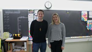 Jimmy Svartström och Jasmin Bilenberg står framför griffeltavlan i ett klassrum.