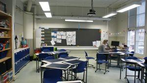 Jasmin Bilenberg sitter i ett tomt klassrum och håller distansundervisning med hjälp av en dator.