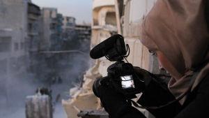 Nainen kuvaa kameralla aleppolaista sotaisaa katutilaa parvekkeelta.
