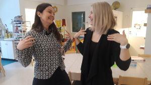 """Angelica Storkamp och Alexandra Östergård visar tecknet för """"glad""""."""