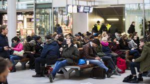 Människor sitter och väntar på Utrecht centralstation i Nederländerna på grund av stormen den 18.1.2017.