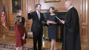 Brett Kavanaugh står med höjd högerhand då han svär domareden.