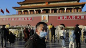 Man med mask framför ansiktet i Kina.