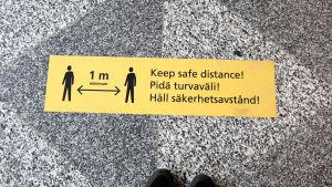 Pidä turvaväli!- tarra lentoaseman lattiassa.
