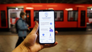 En hand håller upp en telefon med appen Coronablinkern, på en metroperrong.