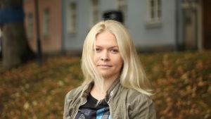 En kvinna med blont hår står vid åstranden och tittar rakt in i kameran.
