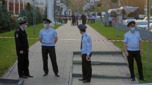 Flera polismän står vid ett avspärrat område.