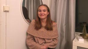 En ung flicka med ljusbrunt hår och beige polotröja sitter vi en spegel och ler.