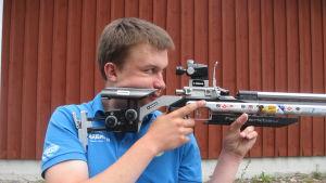 Joni Stenström siktar med ett gevär.
