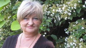 En kvinna med grått hår och med en grön bakgrund bestående av växtlighet. Irene Äyräväinen heter hon.