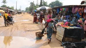 Sandväg kantad av marknadsstånd i det fattiga området Abobo i Elfenbenskusten.