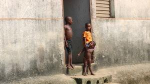 Tre barn står i en dörröppning till ett betonghus i Abobo, Elfenbenskusten.