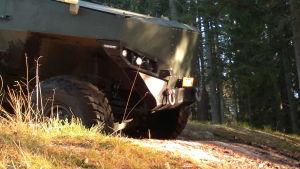 Framhjul och främre ändan av ett Misu-pansarfordon på en skogsväg.