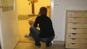Dagispersonal hjälper barn.