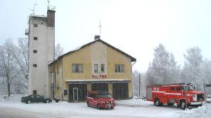 Ett gult hus med brandbilar framför. Det står Pojo FBK på huset.