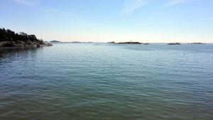 Hav med några holmar, havet är lugnt och himlen är blå.