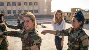 Naissotilaita ja toimittaja heidän kanssaan parijonosso, toinen käsi eteen ojennettuna.