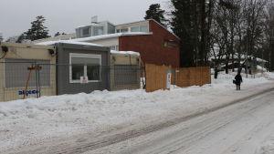 Mäntymäen koulus byggnad med byggmaterial och i förgrunden.