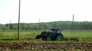 Traktor på åker.