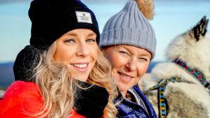 Krista och Lotta sitter utomhus i vintermössor och ler mot kameran.