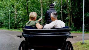 Janne Grönroos och Hasse Brontén med ryggarna mot kameran i en hästdragen vagn.