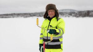 Heimo Pukkila Nellimistä mittaa Inarijärven jäänpaksuutta.