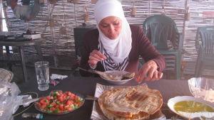 Nada Kettunen lounaalla, leipää ja kalaa syyrialaiseen tapaan.