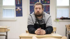 Jarno Jäppinen istumassa vanhan luokkahuoneensa pulpetissa.
