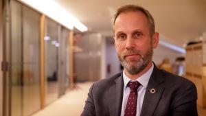 Tjänsteman iklädd grå kostym ser in i kameran. Han befinner sig på Jord- och skogsbruksministeriet.